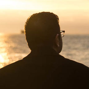 An image of a person's head and shoulders silhouetted against the sunset