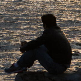 An image of a person sitting by the ocean at dusk, in silhouette