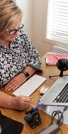 An image of Christine seated at her desk with her videoconferencing equipment