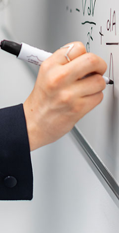 An image of a person's hand writing with a marker on a whiteboard